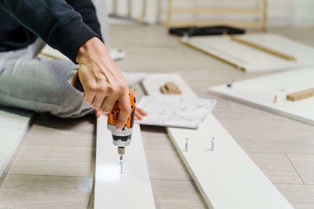 Close up on midsection of unknown caucasian man holding electric screwdriver while putting together Self assembly furniture of plywood screwing screws following instructions - DIY concept copy space