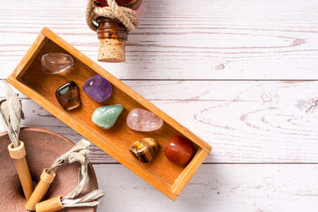 Top down view on seven chakra healing crystal stones for mind body and soul reiki practicing homeopathy alternative medicine on wooden table with copy space