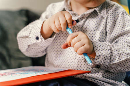 Close up on midsection of small caucasian child boy or girl hodling blue felt pen on the sofa bed at home trying to open or close it while holding in hands - childhood learning development concept