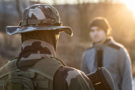 Back view of unknown armed soldier standing against a migrant or terrorist or criminal in sunny evening in nature during border patrol or mission Stock Photo