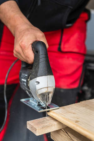 Close up on hand of unknown carpenter working with an electric jigsaw cutting wood with saw woodworking hobby concept copy space