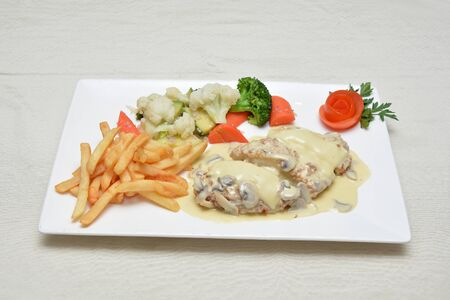 chicken cordon bleu with french fries and vegetable salad served in white plate