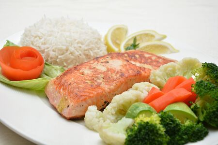 Grilled salmon fillet with fresh vegetable salad close up photo