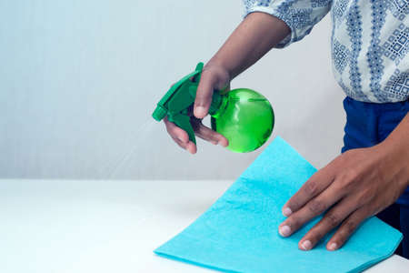 cleaning the table with disinfectant spray, hand only