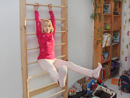 wall bars: Beautiful athletic girl plays sports on Wall bars in the childrens room Stock Photo