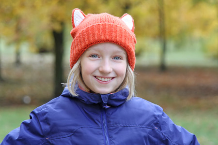 Cheerful blond girl smiling in a funny knitted cap with ears in the form of a fox. Autumn, outdoors.