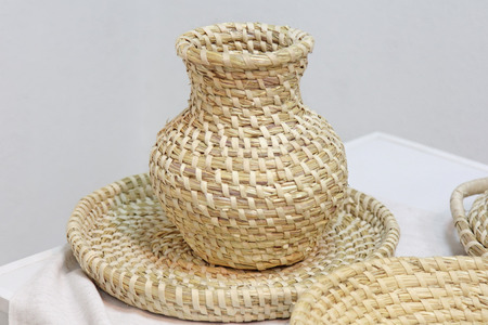 braiding: Crockery braiding of straw - a pitcher and a plate. Homemade ecological shatterproof tableware. Stock Photo