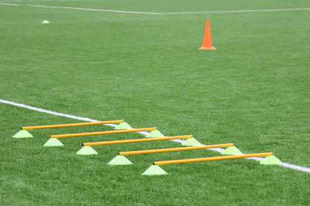 Chips and cone for football training. Sports background with markings on an artificial lawn on a soccer field.