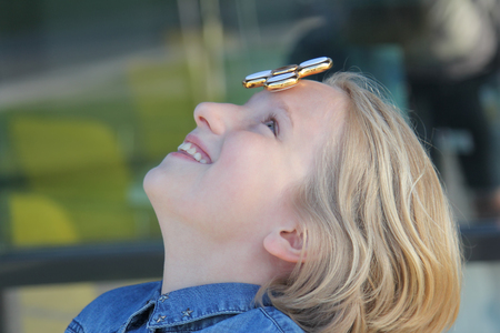 Cheerful cute school aged girl playing with a gold fidget spinner. A popular trendy toy spins on the forehead.
