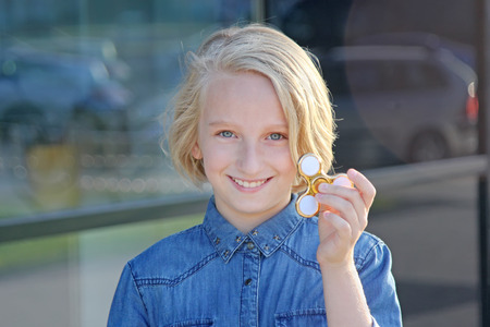 A beautiful school girl playing with a gold fidget spinner. Popular toy.