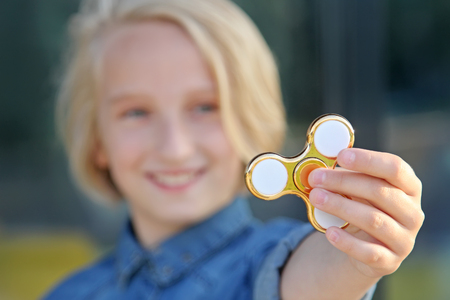 Cheerful school girl playing with gold fidget spinner. A popular trendy toy. Stock Photo