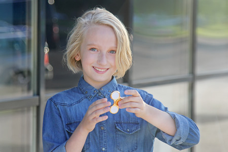 Beautiful cheerful girl playing with a gold fidget spinner. A popular trendy toy for the development of fine motor skills in children and adults.