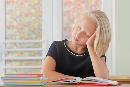 Tired child schoolgirl sleeps during a lesson at the desk in a classroom