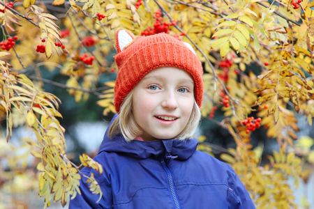 Cheerful kid smiling, the child is dressed in a funny knitted warm hat with ears, looks like a fox. Autumn, outdoors portrait with yellow leaves and rowan berries.