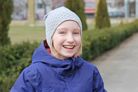 Cheerful preteen girl 9-11 year old laughing on a walk outdoors. Wearing warm jacket and hat.