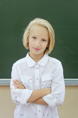 Portrait of adorable schoolgirl 9-11 years old in a classroom near a chalkboard. Girl dressed in stylish shirt. Back to school.