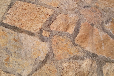 Old stone wall. Uneven rough stones of different shapes. Stone background.