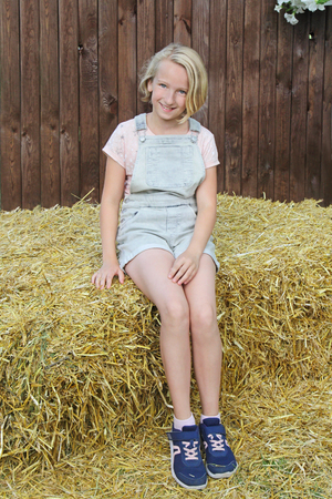 Beautiful happy preteen girl dressed in short bib overalls sitting on a hay in the village. Country style.