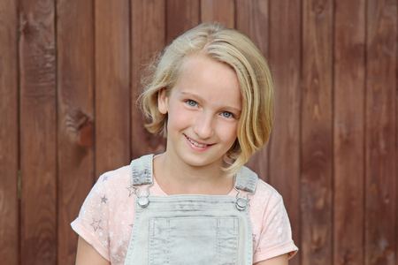 Bella y feliz niña rubia sonríe. Retrato en el fondo de una pared de madera. Foto de archivo