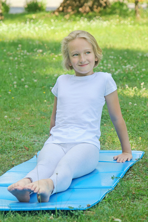 School-age girl in light clothes rests and plays sports on the mat in the park. Yoga and relaxation.