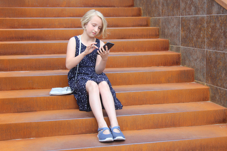 Stylish preteen girl using a phone sitting on a rusty staircase in a modern building. Child and gadget concept. Stock Photo