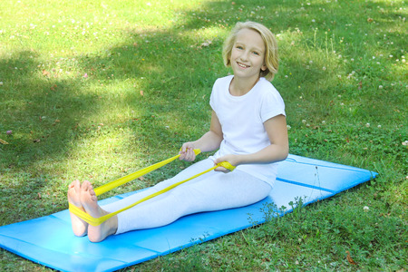 Adorable school aged kid playing with a rubber band and mat outdoors in the park. Healthy lifestyle. Outdoors workout.