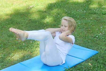 Beautiful blonde preteen girl in light clothing practicing yoga on a mat in the park. Healthy lifestyle. Outdoors workout. 免版税图像 - 106641459