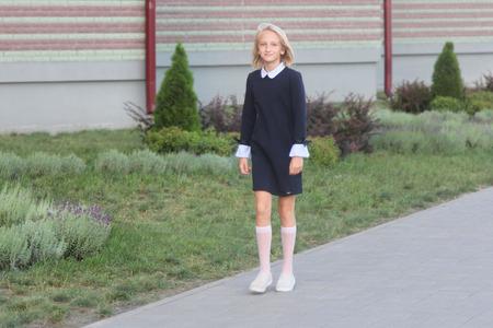Schönes blondes Mädchen im eleganten Kleid geht zur Schule. Zurück zur Schule. Standard-Bild