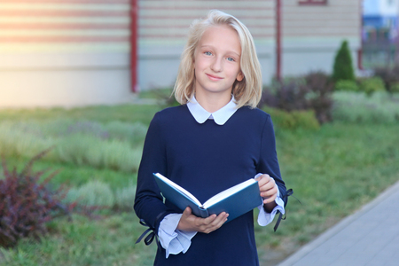 Beautiful blonde girl in elegant dress with book in hands near school. Schoolgirl likes to learn and read.