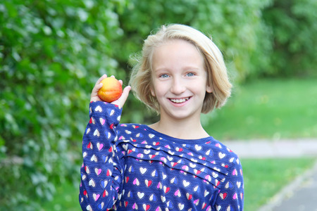 Beautiful blonde girl in the park eats fruit, nectarine or peach. Healthy food for children. Banco de Imagens