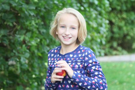 Schönes blondes Mädchen im Park isst Obst, Nektarine oder Pfirsich. Gesundes Essen für Kinder. Standard-Bild