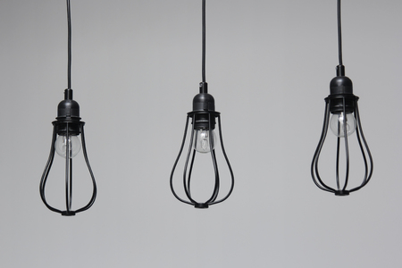 Three incandescent light bulbs on gray background. Decorative lighting. 版權商用圖片
