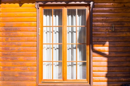sipario chiuso: wooden wall with a large window, closed the curtain on which falls the shadow Archivio Fotografico