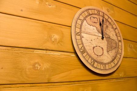 numeros romanos: Reloj grande de color amarillo con n�meros romanos en una pared de madera muestra doce