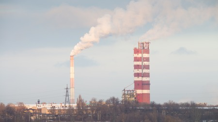 tall chimney: Industrial factory smoking chimneys against the sky and residential buildings