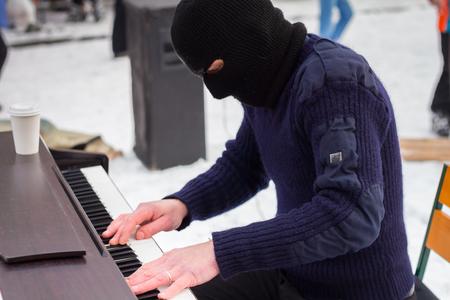 pianista: Un pianista toca en una máscara de negro en la calle Foto de archivo