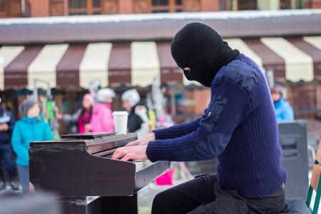 pianista: Un pianista toca en una m�scara de negro en la calle Foto de archivo