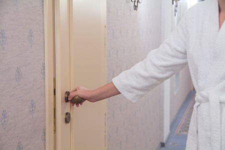A girl in a white coat opens the door in the hotel