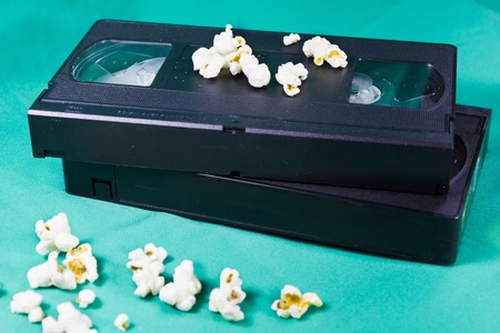 superseded: The old videotapes and popcorn on a green background