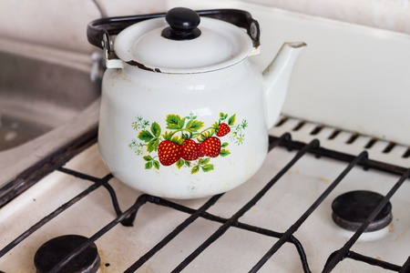old gas stove: White teapot with a floral print stands an old gas stove
