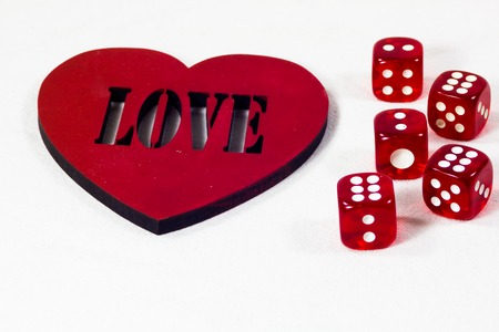 Red dice near the heart on a white background