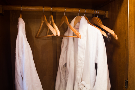 housecoat: White Hotel gown on a hanger in a brown wardrobe Stock Photo
