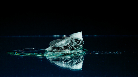 five cents: Five cents frozen in melting ice on the black background