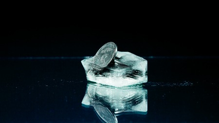 melting ice: Five cents frozen in melting ice on the black background