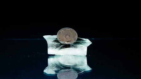 cents: Five cents frozen in melting ice on the black background