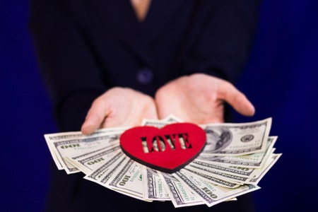 fan shaped: Hands of girl holding a fan of hundred dollars on them are red heart with love Stock Photo