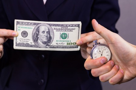 women's hand: Money in the of womens hand and stopwatch in the mans hand