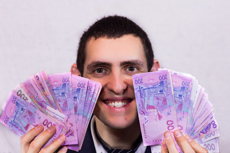 20   24: Happy man holding a lot of Ukrainian hryvnia and rejoices