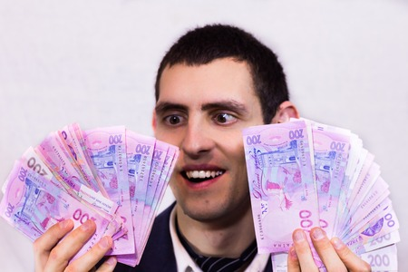 20 24 years: Happy man holding a lot of Ukrainian hryvnia and rejoices