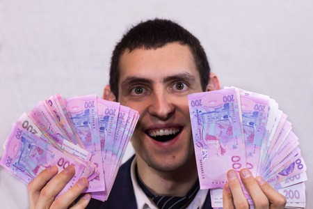 rejoices: Happy man holding a lot of Ukrainian hryvnia and rejoices